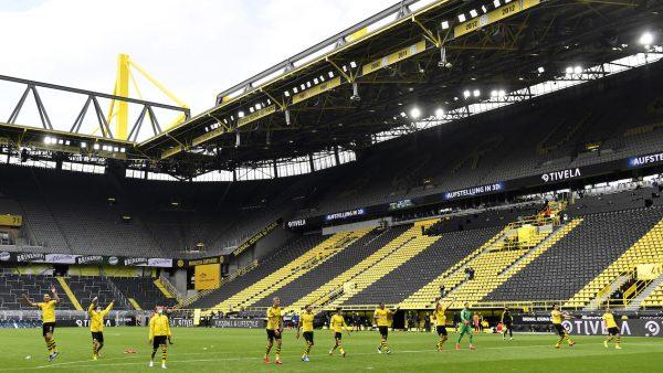 Os jogadores do Borussia celebram a goleada por 4 a 0 sobre o Schalke 04 com as arquibancadas do Signal Iduna Park completamente vazias.
