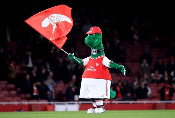 O mascote do Arsenal, Gunnersaurus, dentro de campo com a bandeira do clube na mão direita.