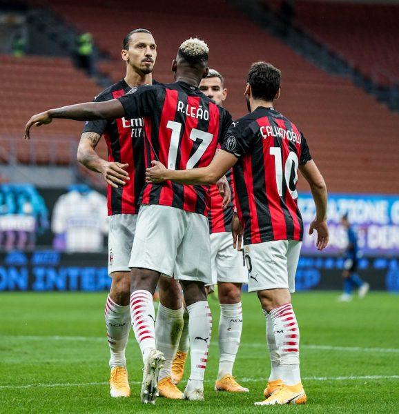 Os jogadores do Milan se abraçam em campo para celebrar a vitória sobre a Internazionale, no derby de Milão.