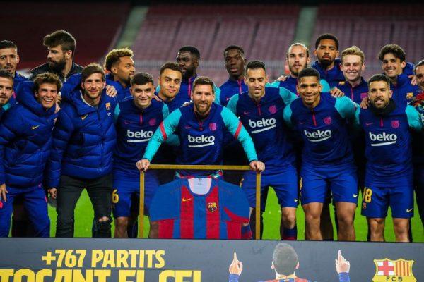 Leo Messi ao lado dos seus companheiros e da camisa autografada por eles.