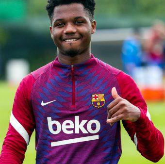 Ansu Fati sorrindo e fazendo o sinal de positivo com a mão esquerda no campo de treinamento.