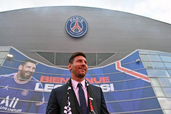 Messi, de terno e sorrindo, durante a sua apresentação em Paris.
